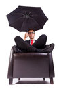 Man sitting in comfortable armchair with umbrella Royalty Free Stock Photo