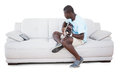 Man sitting on couch learning to play guitar with his tablet pc Royalty Free Stock Photo
