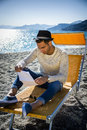Man sitting on deckchair while reading letter Royalty Free Stock Photo