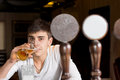 Man sitting drinking at a pub view past the beer taps behind the counter of young alone beer the counter in or nightclub with Royalty Free Stock Image