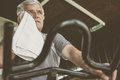 Man sitting on exercise machine. Man wipes his face with
