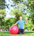 Man sitting on an exercising mat and giving thumb up Stock Photography