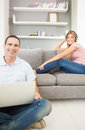 Man sitting on floor using laptop with woman listening to music Royalty Free Stock Photo