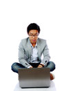 Man sitting on the floor and using laptop young asian over white background Stock Photo