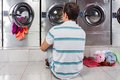 Man sitting in front of washing machines rear view young on floor at laundromat Royalty Free Stock Photo