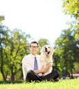 Man sitting on a grass and hugging his labrador retriever dog in green park shot with tilt shift lens Stock Images