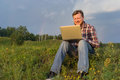 Man sitting on the grass with a laptop Royalty Free Stock Photo
