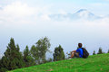 Man sitting on grass and looking mountain Royalty Free Stock Photo