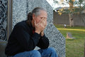 Man sitting at gravesite Royalty Free Stock Images