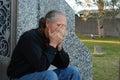 Man sitting at gravesite Royalty Free Stock Photo