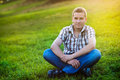 Man sitting on the green grass in the park hadsome Stock Photography