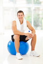Man sitting gym ball cheerful young on holding water bottle Royalty Free Stock Image