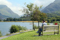 Man sitting by a lake on bench looking at beautiful this was taken at llanberis wales in the united kingdom Stock Photo
