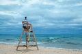 Man sitting on lifeguard chair Royalty Free Stock Photo