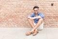 Man sitting near brick wall and smiles Royalty Free Stock Photo