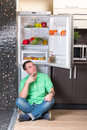 The man sitting next to open refrigerator Royalty Free Stock Photo