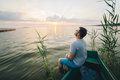 Man sitting in the old boat thinking Royalty Free Stock Photo