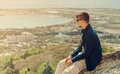 Man sitting on peak of mountain and looking at town Royalty Free Stock Photo