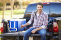 Man sitting in pick up truck on camping holiday wearing rucksack smiling Royalty Free Stock Photo