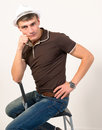 Man sitting poses posing while on a chair Royalty Free Stock Photo