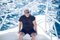 Man sitting on the prow of a boat high angle view middle aged wearing sunglasses hot summer day Stock Photography