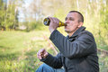 Man sitting on the rails drinking beer Royalty Free Stock Photo