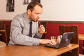 Man sitting in restaurant with laptop and phone handsome alone computer mobile he is eating traditional english breakfast fried Stock Photos