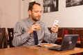Man sitting in restaurant with laptop and phone handsome alone computer mobile he is eating traditional english breakfast fried Royalty Free Stock Photo