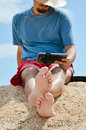 Man sitting at seaside with tablet computer and resting young on sandy beach on summer outdoors background Stock Photos