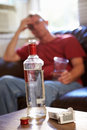 Man sitting on sofa with bottle of vodka and cigarettes unhappy in foreground Stock Photography