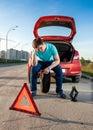 Man sitting on spare wheel near broken car depressed Royalty Free Stock Photography