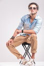 Man sitting on a stool while looking up cute fashion rsting his hands his knee Stock Photo