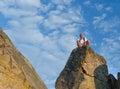 Man sitting on top of a mounain wearing rucksack rocky pinnacle mountain peak against blue summer sky Stock Images