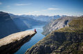 Stock Photo Man sitting on trolltunga in norway