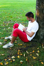 Man sitting under a tree reading a book Royalty Free Stock Image