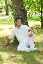 Man sitting under a tree in white Stock Image