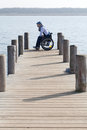 Man sitting in wheelchair outside nature a long boardwalk at a lake Royalty Free Stock Photography