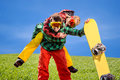Man in ski suits giving piggyback ride to girlfriend with snowbo snowboard on the grass under the sky Stock Photos