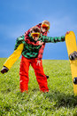Man in ski suits giving piggyback ride to girlfriend with snowbo snowboard on the grass under the sky Stock Image