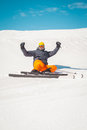 Man skier sitting on snow waving hands excited Royalty Free Stock Photo
