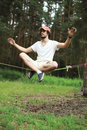 Man slacklining balancing on a rope slackline in forest sport leisure recreation and healthy lifestyle concept Royalty Free Stock Photos