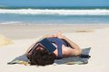 Man sleeping on secluded beach with book covering face young Stock Photos