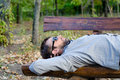 Man sleeping on a wooden bench Stock Photo