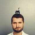 Man with small bored man portrait of dissatisfied on the head Stock Image