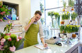 Man with smartphone making notes at flower shop people sale retail business and floristry concept happy smiling florist calling on Stock Image