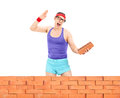 Man smashing a brick behind a wall isolated on white background Royalty Free Stock Photos