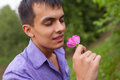Man smelling a flower Stock Photo