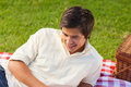 Man smiling as he lie on a picnic blanket Royalty Free Stock Photos