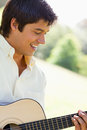 Man smiling as he plays a guitar Stock Images