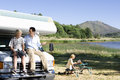 Man smiling at son on bonnet of motor home by lake mother reading in background Stock Image